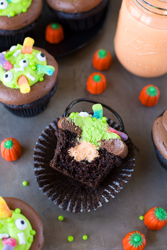 """Witch's Cauldron Cupcake with a bite missing to show the Orange """"Scream"""" Filling"""