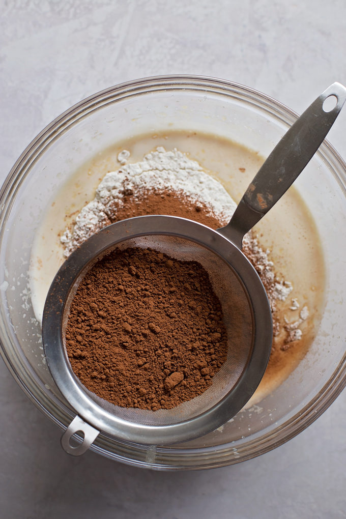 Cocoa powder in a mesh sieve for this everyday chocolate cake. | lifemadesimplebakes.com