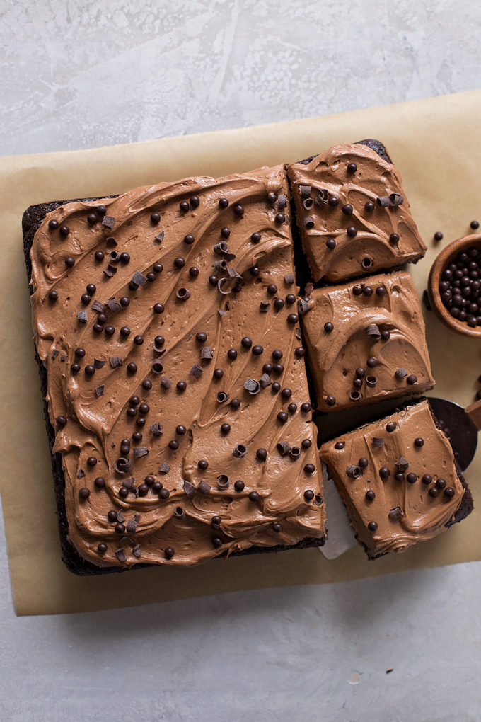 Cutting into the everyday chocolate cake topped with chocolate curls and crunchy chocolate pearls. | lifemadesimplebakes.com