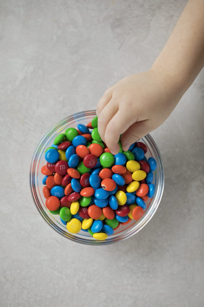 A bowl of colorful chocolate filled candies for M&M cookie bars. | lifemadesimplebakes.com