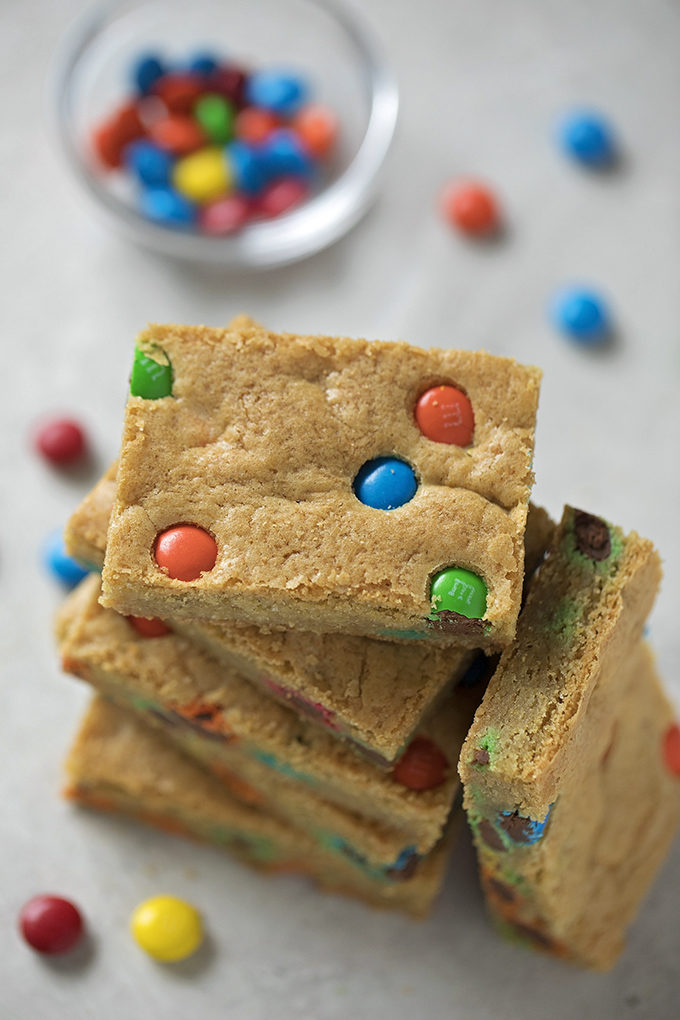 A tall stack of M&M cookie bars. | lifemadesimplebakes.com