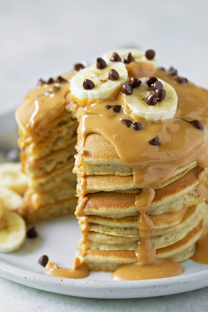 A tall stack of perfect peanut butter banana pancakes with drizzled peanut butter on top.   lifemadesimplebakes.com
