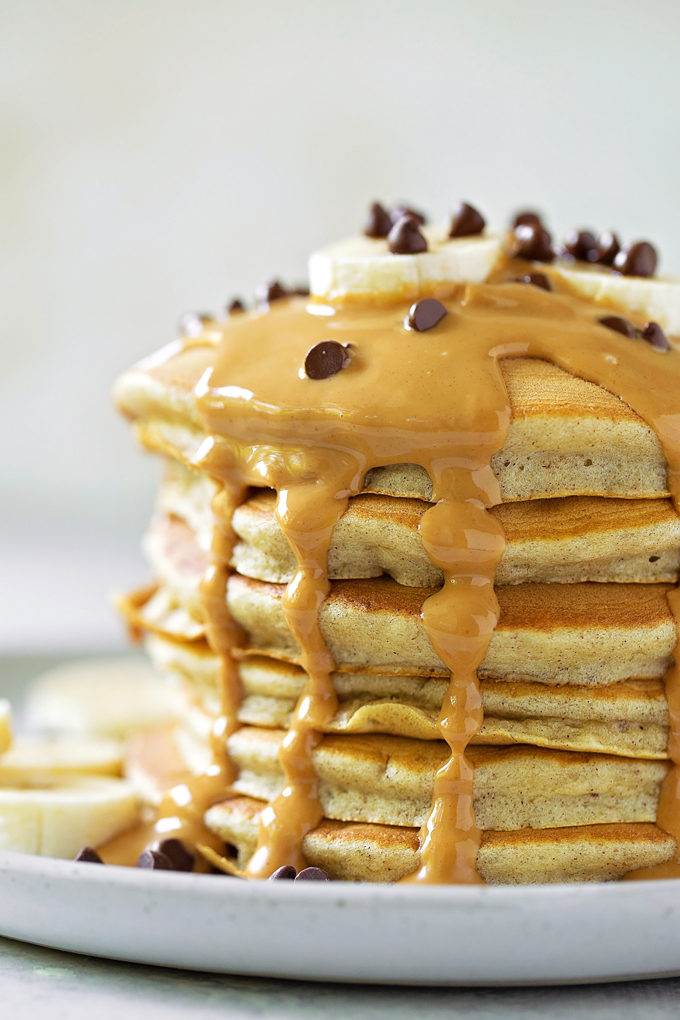 A stack of easy and delicious peanut butter banana pancakes topped with slices of banana and mini chocolate chips. | lifemadesimplebakes.com