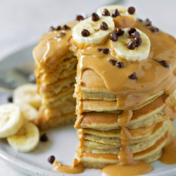 A stack of peanut butter banana pancakes with a slice taken out. | lifemadesimplebakes.com