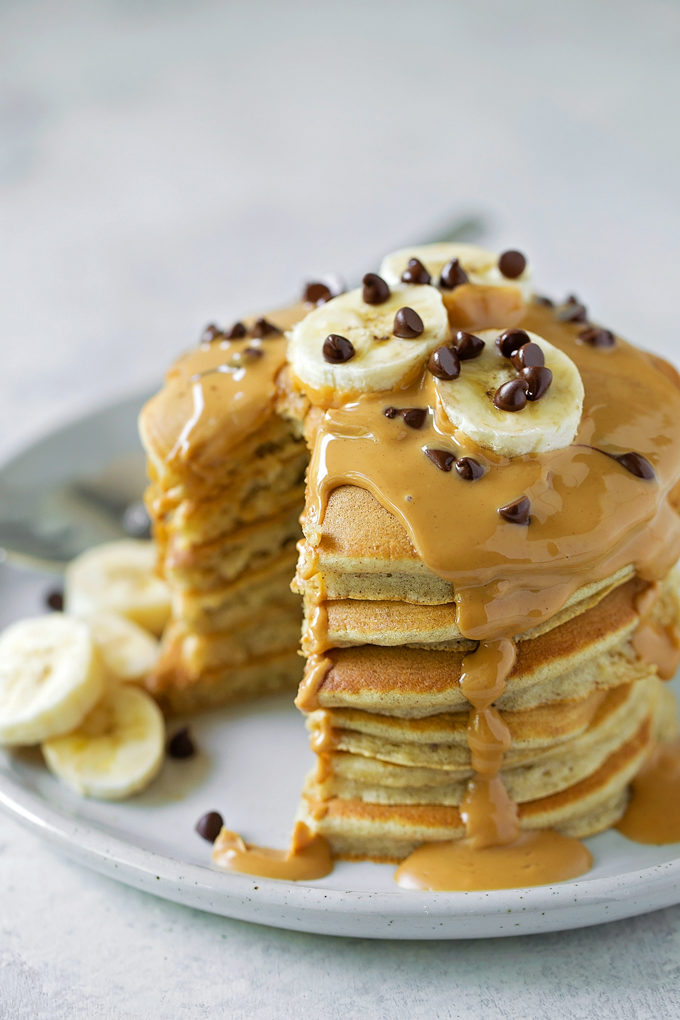 A stack of fluffy peanut butter banana pancakes with peanut butter drizzled on top. | lifemadesimplebakes.com