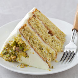 A slice of pistachio layer cake on a plate with a fork. | lifemadesimplebakes.com