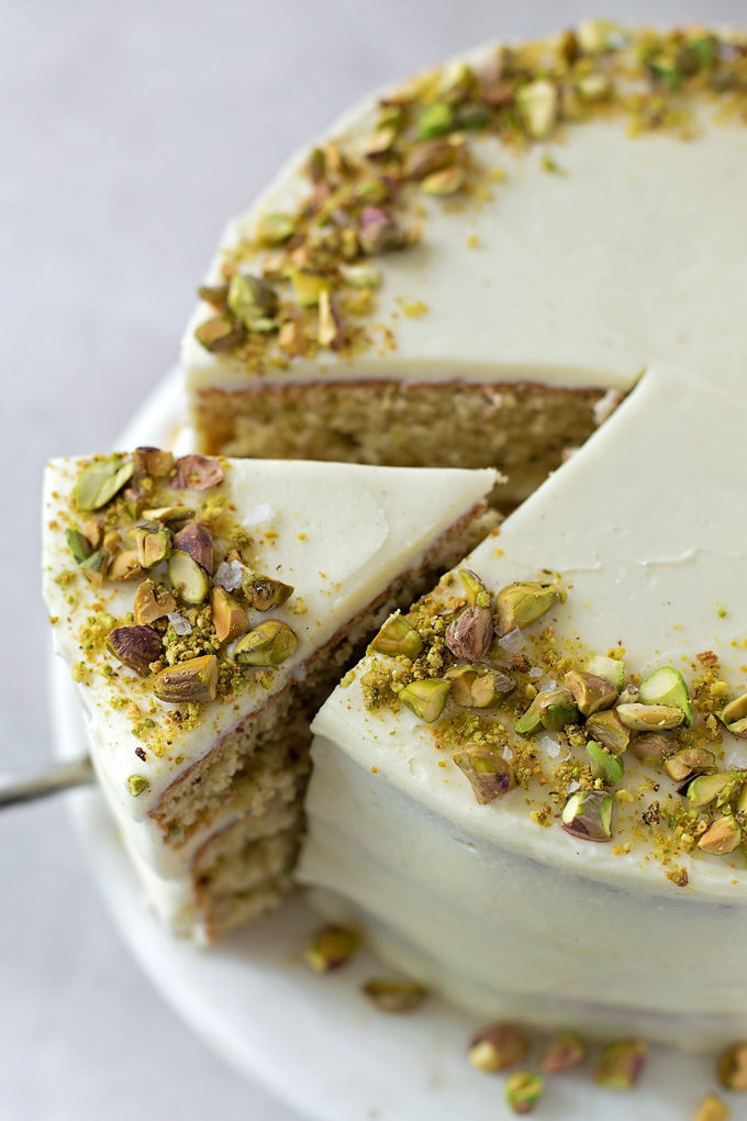 Taking a slice out of the pistachio layer cake with mascarpone frosting. | lifemadesimplebakes.com