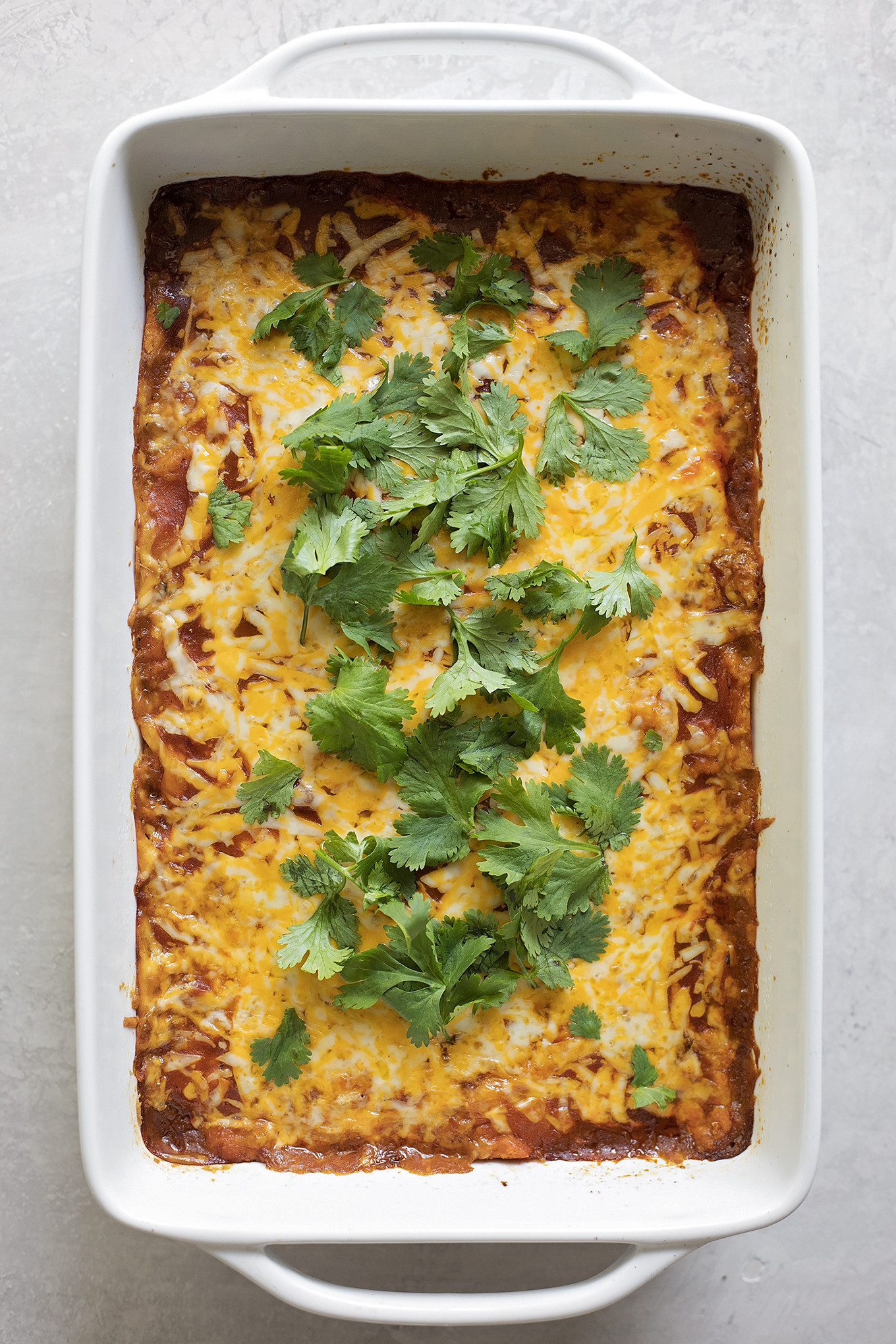 A 9x13 pork tamale casserole with cilantro on top. | lifemadesimplebakes.com