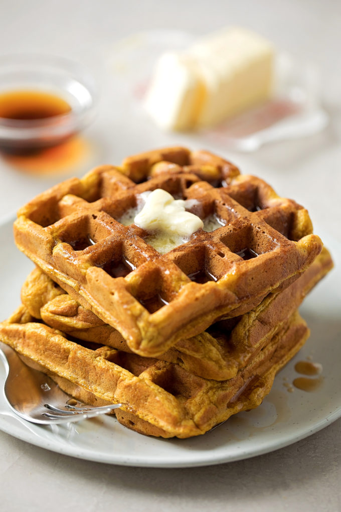 A stack of crispy pumpkin spice waffles topped with butter.