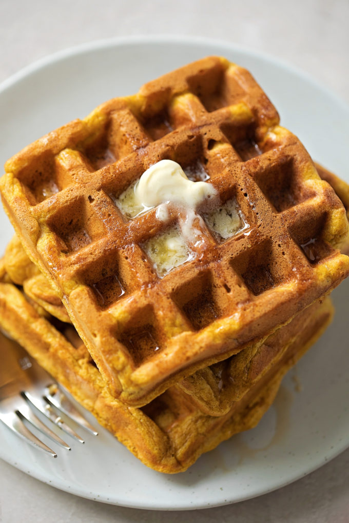 Pumpkin spice waffles piled high with a drizzle of maple syrup and a pat of butter.