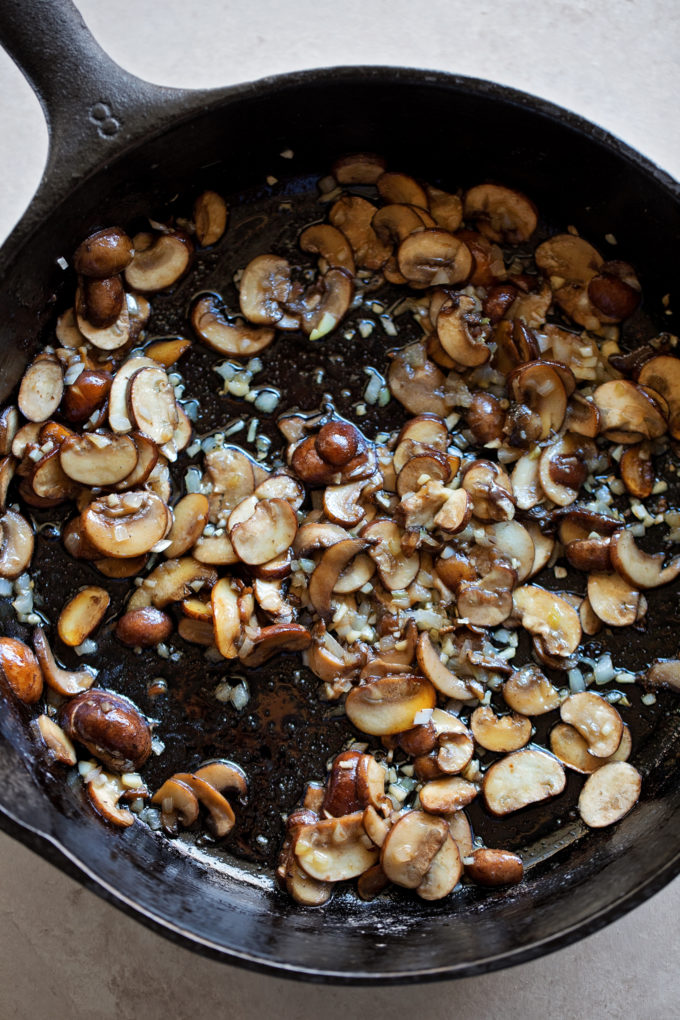 A cast iron skillet with browned mushrooms, garlic and shallot for creamy green bean casserole.
