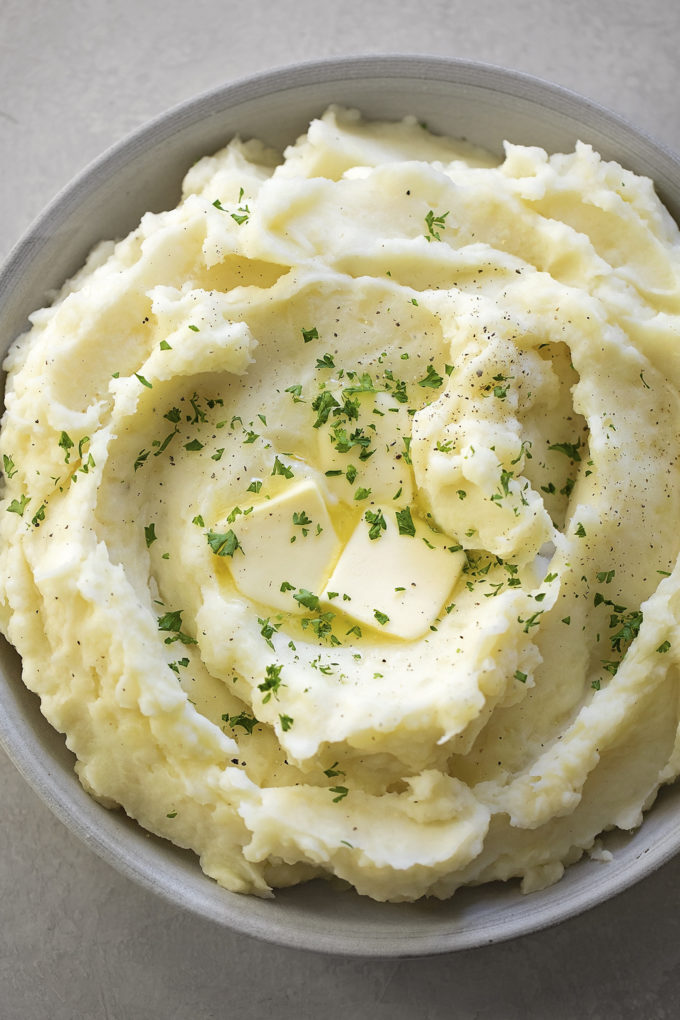 A bowl of Instant Pot mashed potatoes with butter and parsley on top.