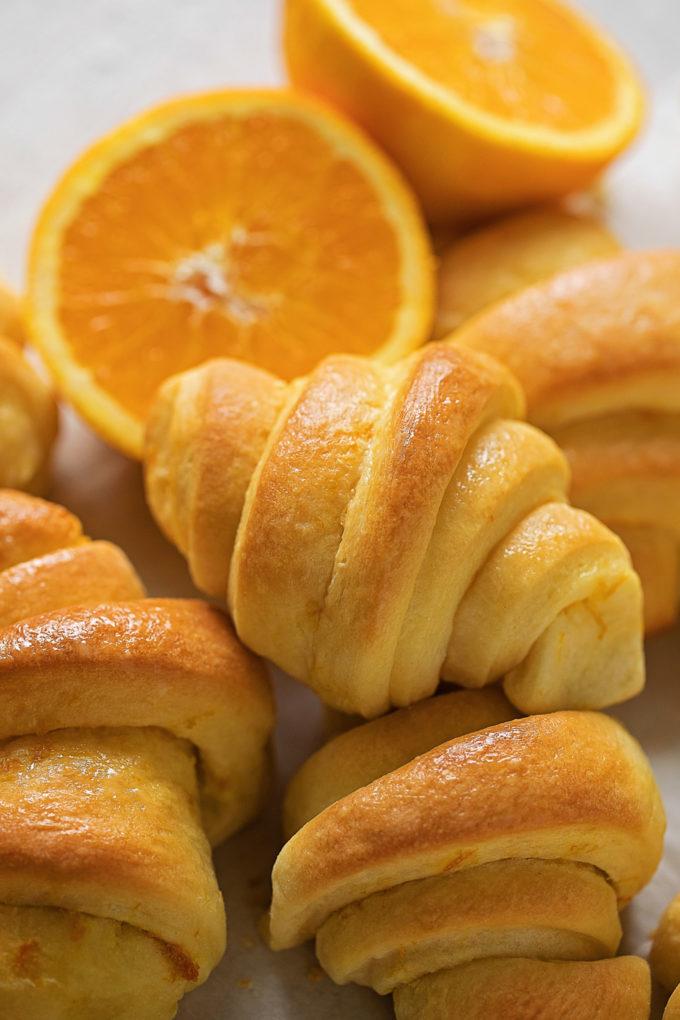Orange dinner rolls with fresh orange halves.