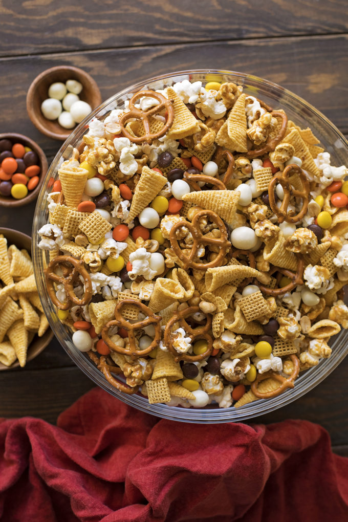 A bowl of Thanksgiving snack mix with ingredients.