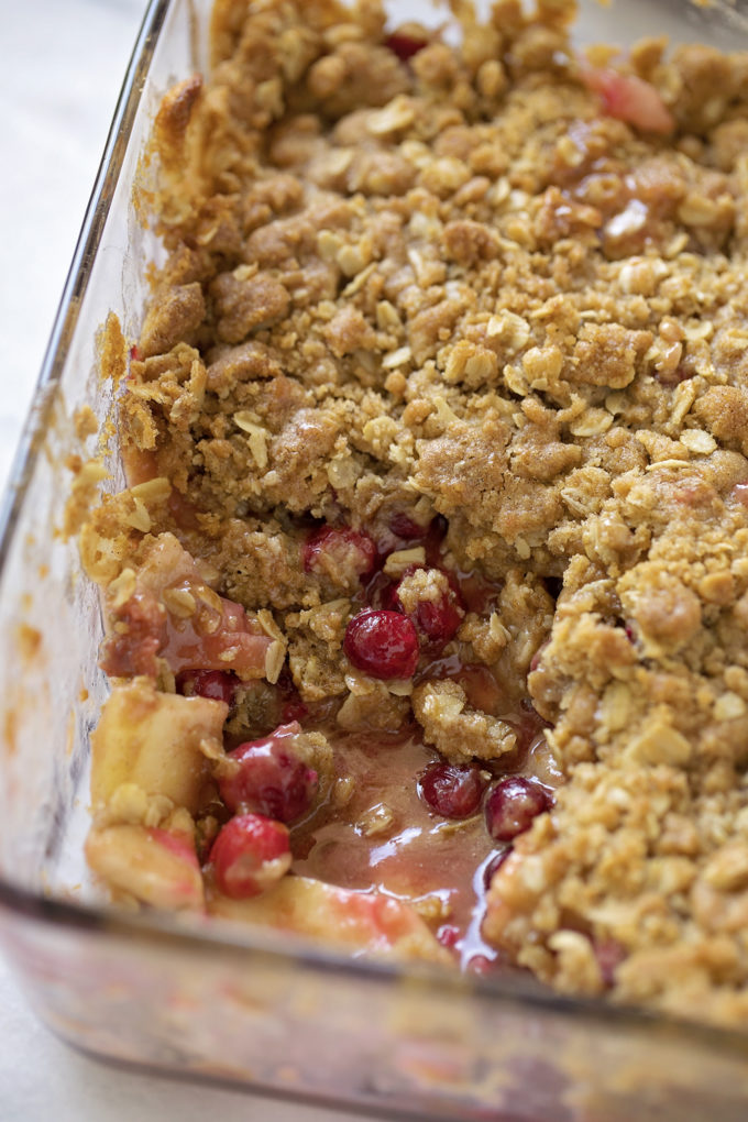 A baking dish of the best cranberry apple crisp, a serving has been removed.