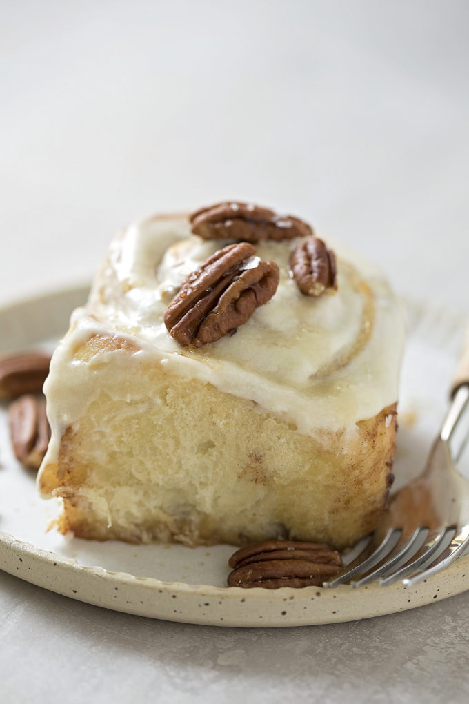 A close up of a frosted maple pecan cinnamon roll on a plate.