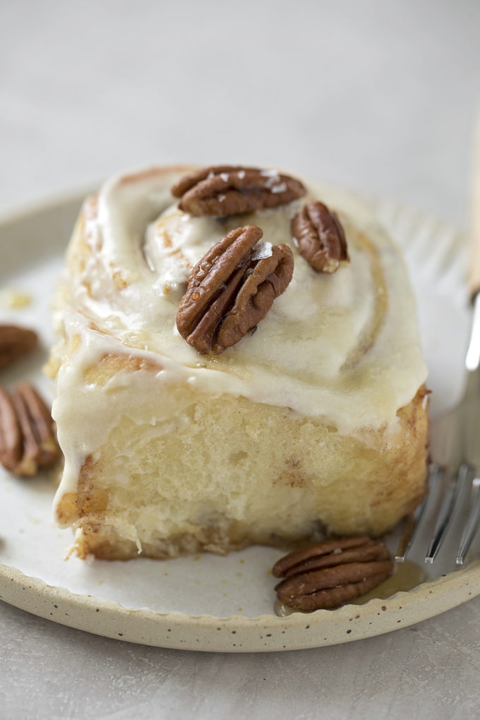 A maple pecan cinnamon roll fresh from the oven and served up with pecans and a drizzle of maple syrup.