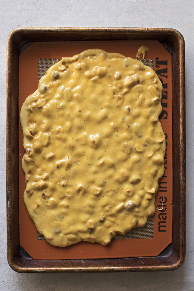 Microwave peanut brittle on a lined sheet pan, cooling and ready to be broken.