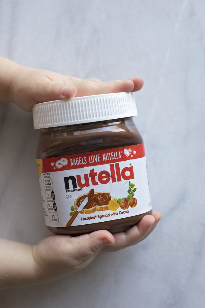 Tiny hands holding a jar of Nutella for the filling of the Nutella puff pastry snowflake.