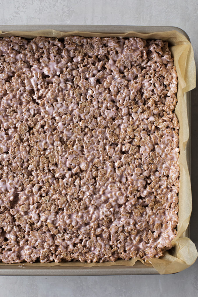 The base of the peppermint rice krispie treats, pressed into a lined 9x9-inch baking pan.