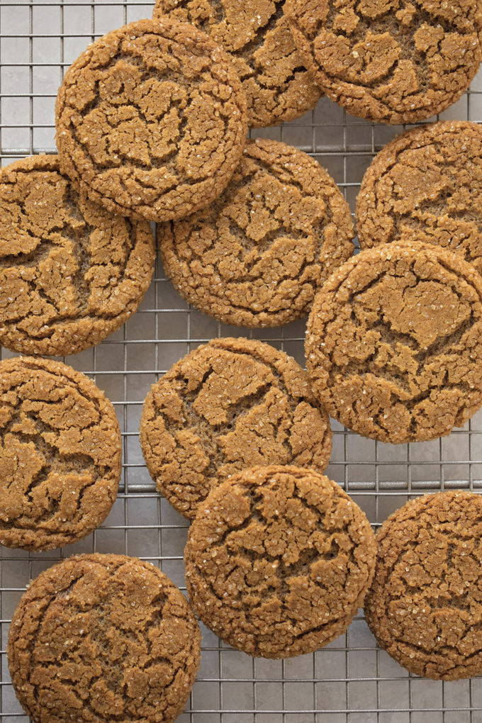 An overhead view of a wire rack with freshly baked sparkling ginger molasses cookies on it.
