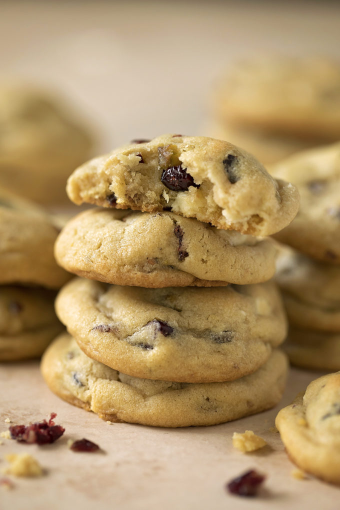 A pile of white chocolate cranberry pistachio cookies with a broken cookie on top.