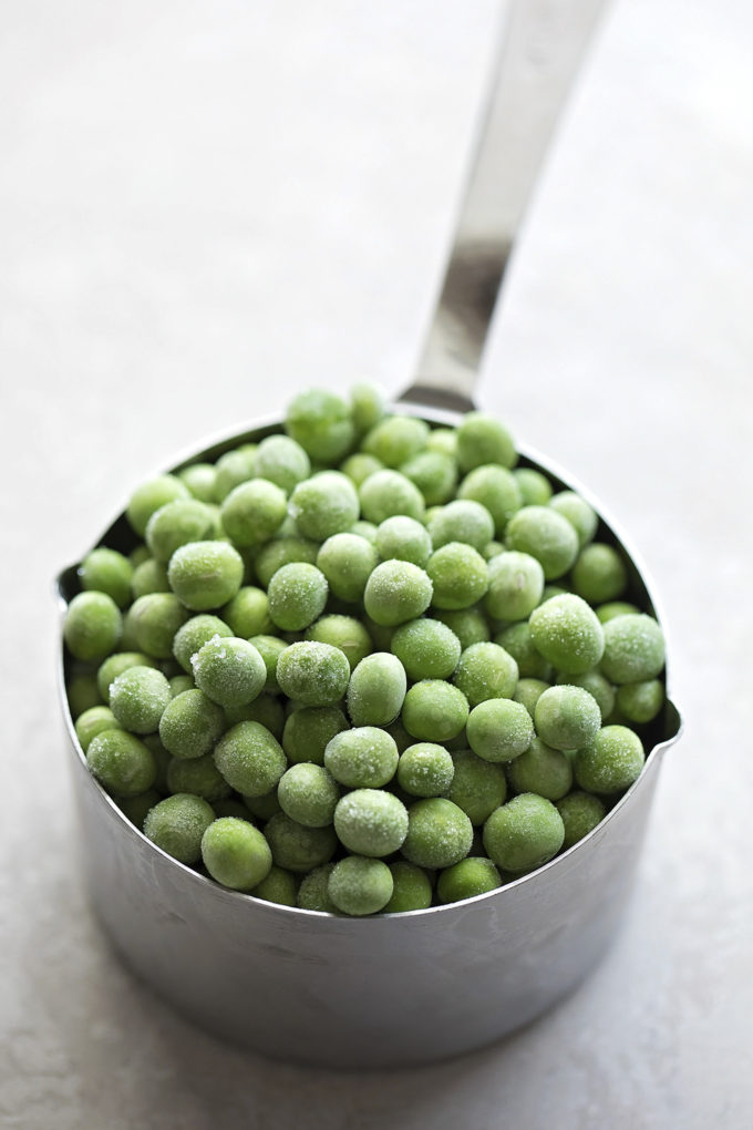 A cup of frozen peas for the chicken, sausage, and rice skillet.