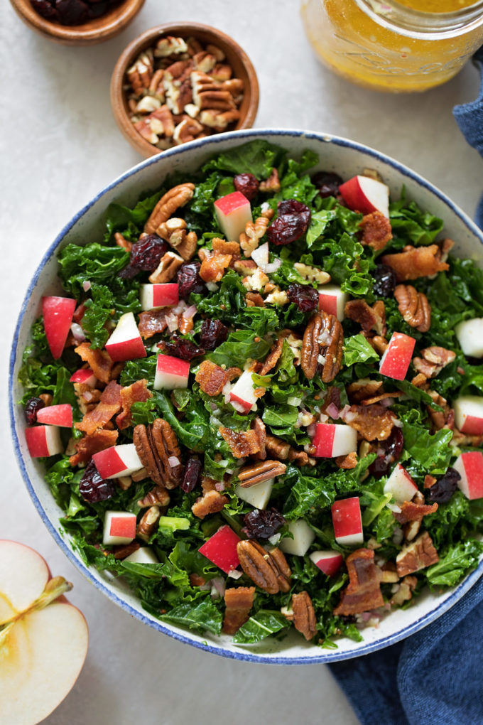 A close up of a bowl of tossed cranberry apple pecan kale salad.
