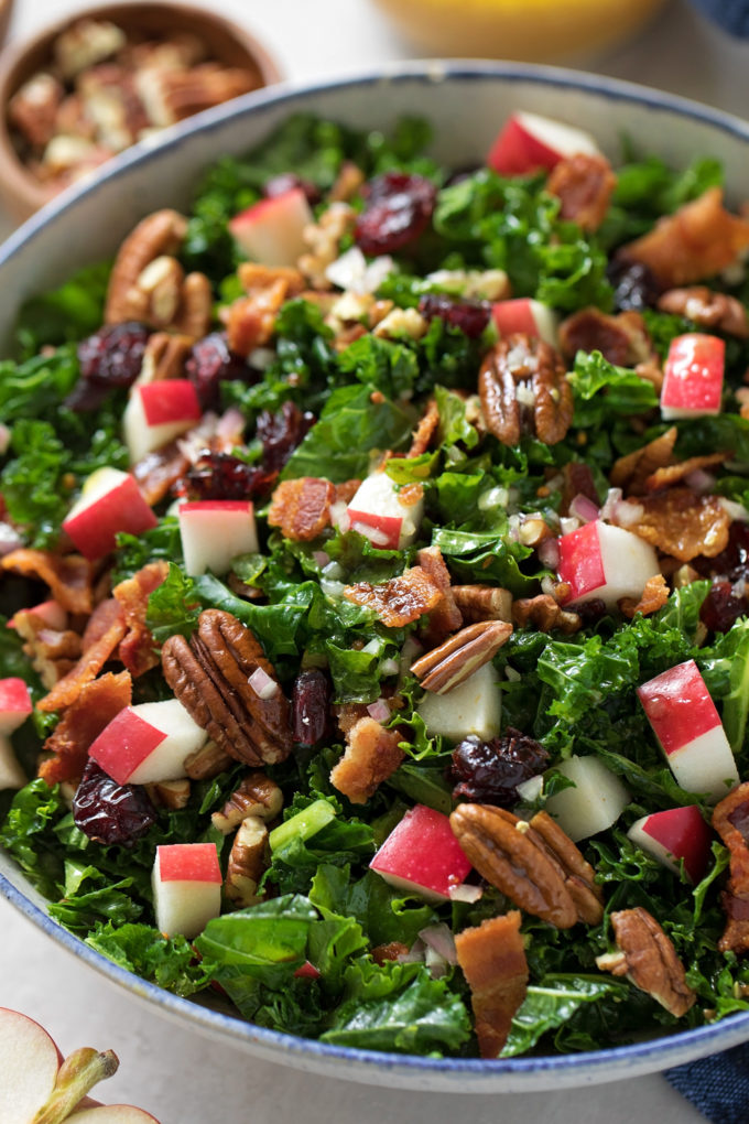 A big bowl of cranberry apple pecan salad with crumbled bacon.