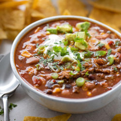 A close up image of easy taco soup garnished with cilantro, sour cream and green onions.
