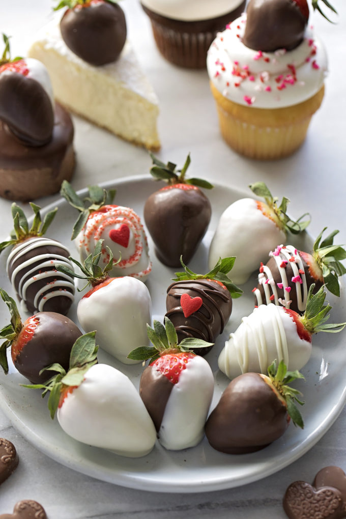 Step by step instructions for how to make perfect chocolate covered strawberries - a plate of dipped strawberries with various ways to use them on desserts.