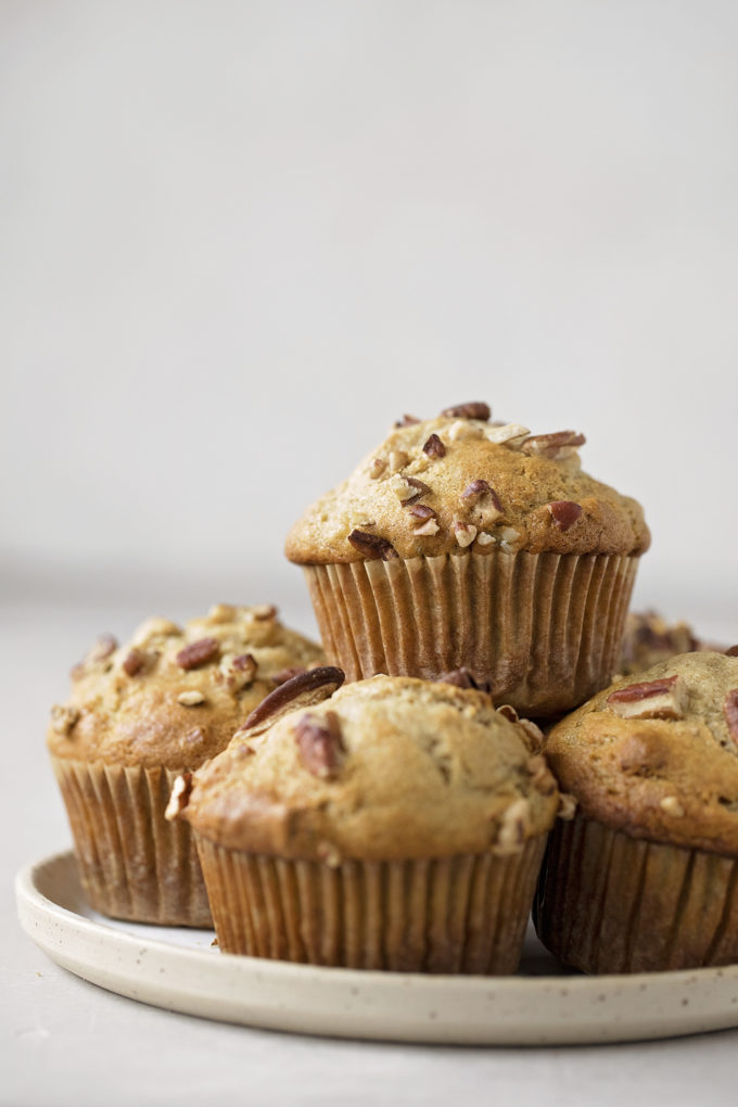 A pile of freshly baked banana nut muffins on a plate.