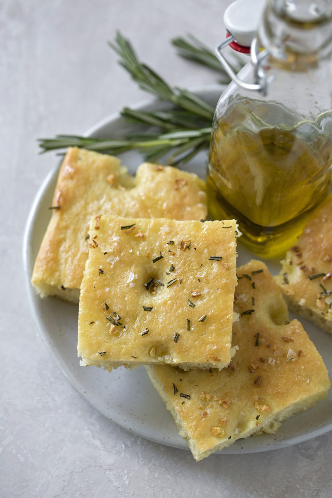 A plate with easy focaccia cut into squares served with olive oil and fresh herbs.