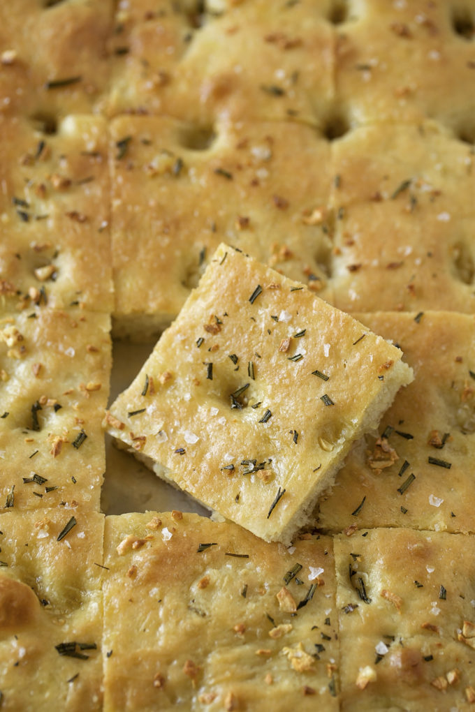 A sheet pan full of easy focaccia with a piece cut out.