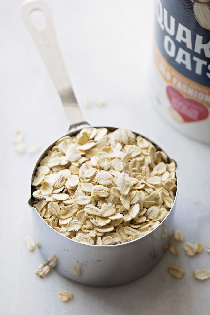 A measuring cup of old fashioned oats ready to be added to the trail mix oatmeal cookie dough.