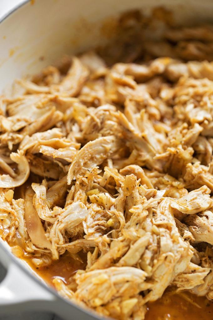 A skillet full of the chicken filling used in chicken tortilla casserole.