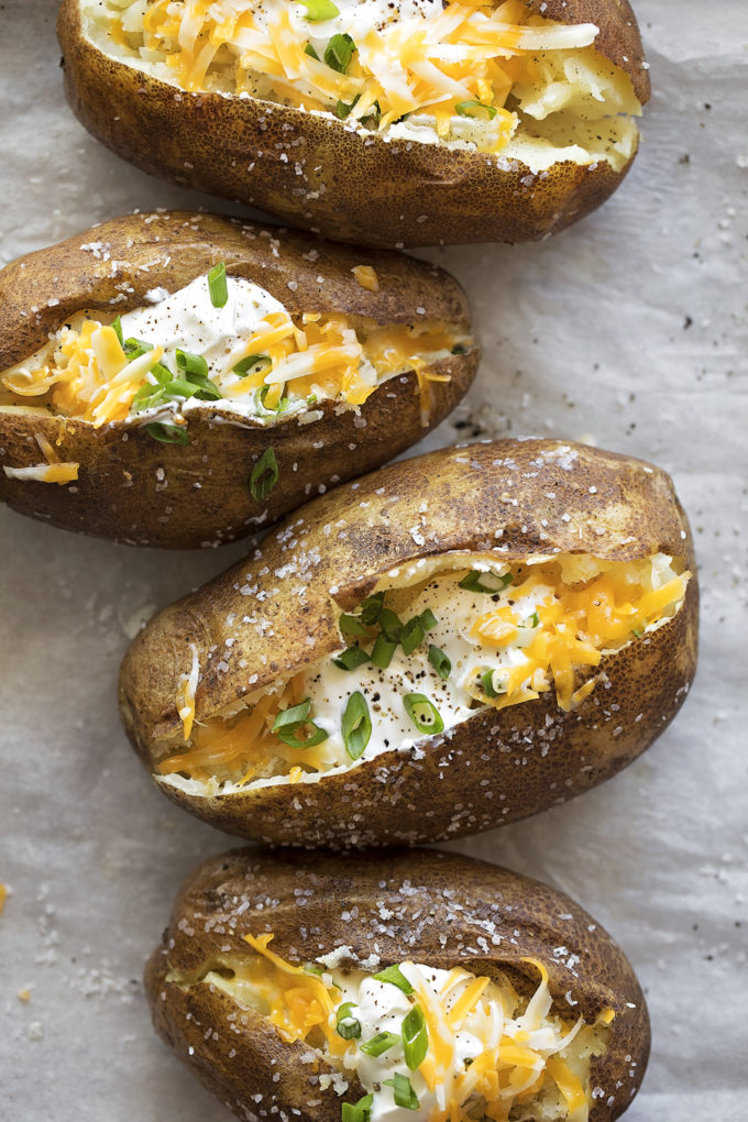 A lined baking sheet with dressed easy Instant Pot Baked Potatoes.
