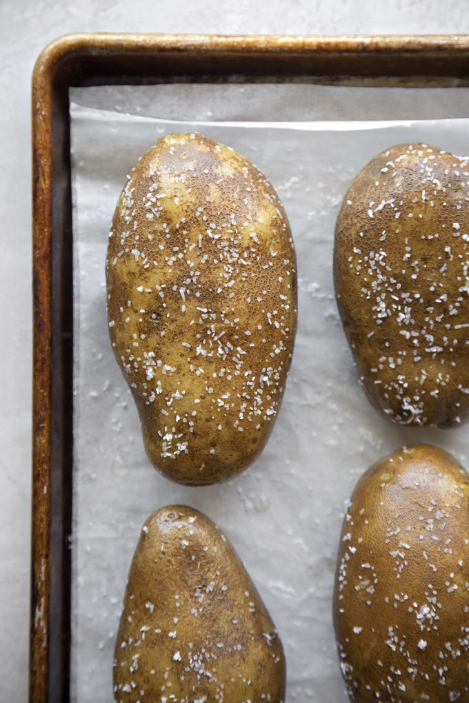 Oil rubbed and salted potatoes on a baking sheet ready to be roasted.