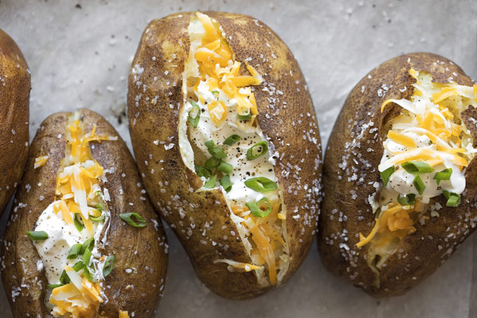 Fully loaded easy Instant Pot baked potatoes lined up on a baking sheet.