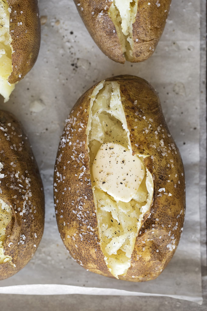 A fully cooked easy Instant Pot baked potato with butter and freshly cracked pepper.