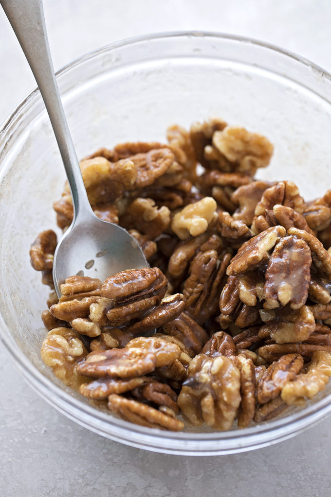 Perfect candied nuts are tossed in a sugar spice coating before being baked.