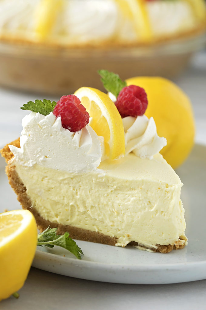 A slice of heavenly lemon cream pie topped with fresh whipped cream and garnished with lemon slices and raspberries.