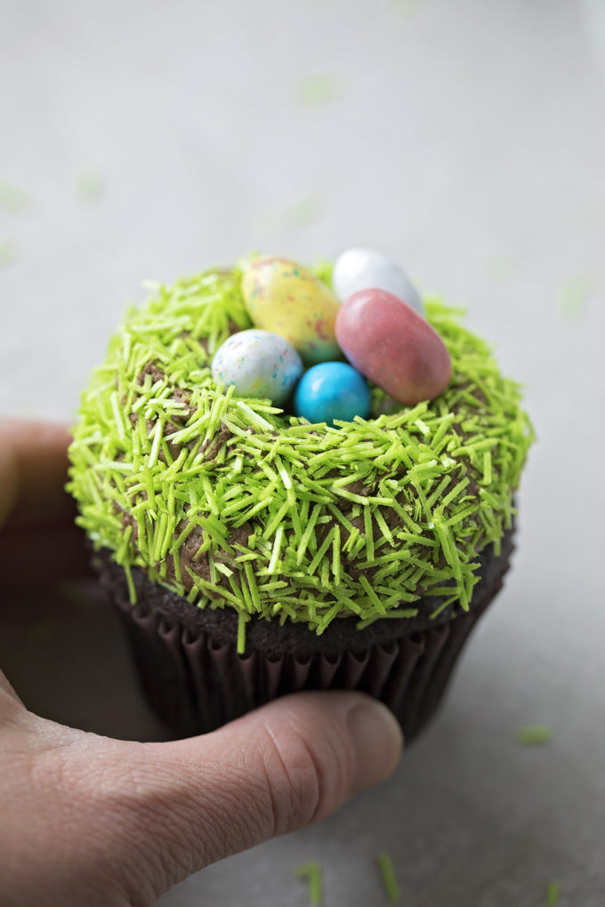 A hand holding a festive malted chocolate nest cupcake.