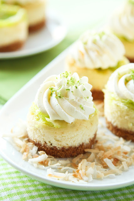 A plate of mini coconut lime cheesecakes on a bed of toasted coconut